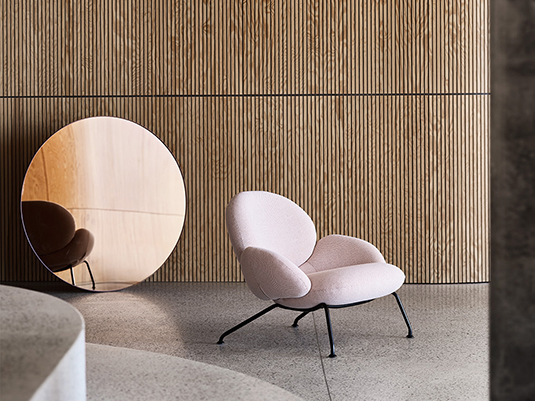 kreslo baixa v ruzovej farbe od softlinu pri drevenej stene