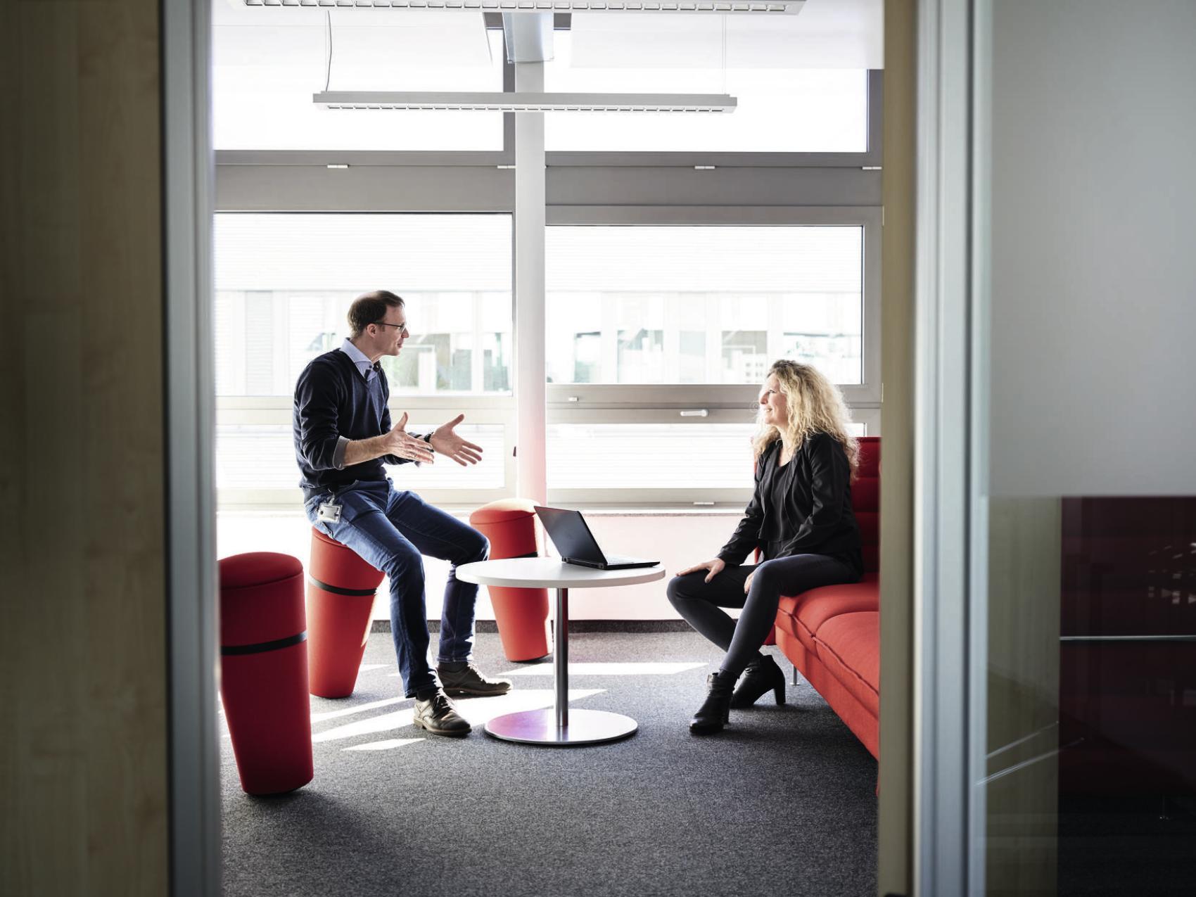 muz a zena pracuju v kancelarii a komunikuju na nabytku od wilkhahnu