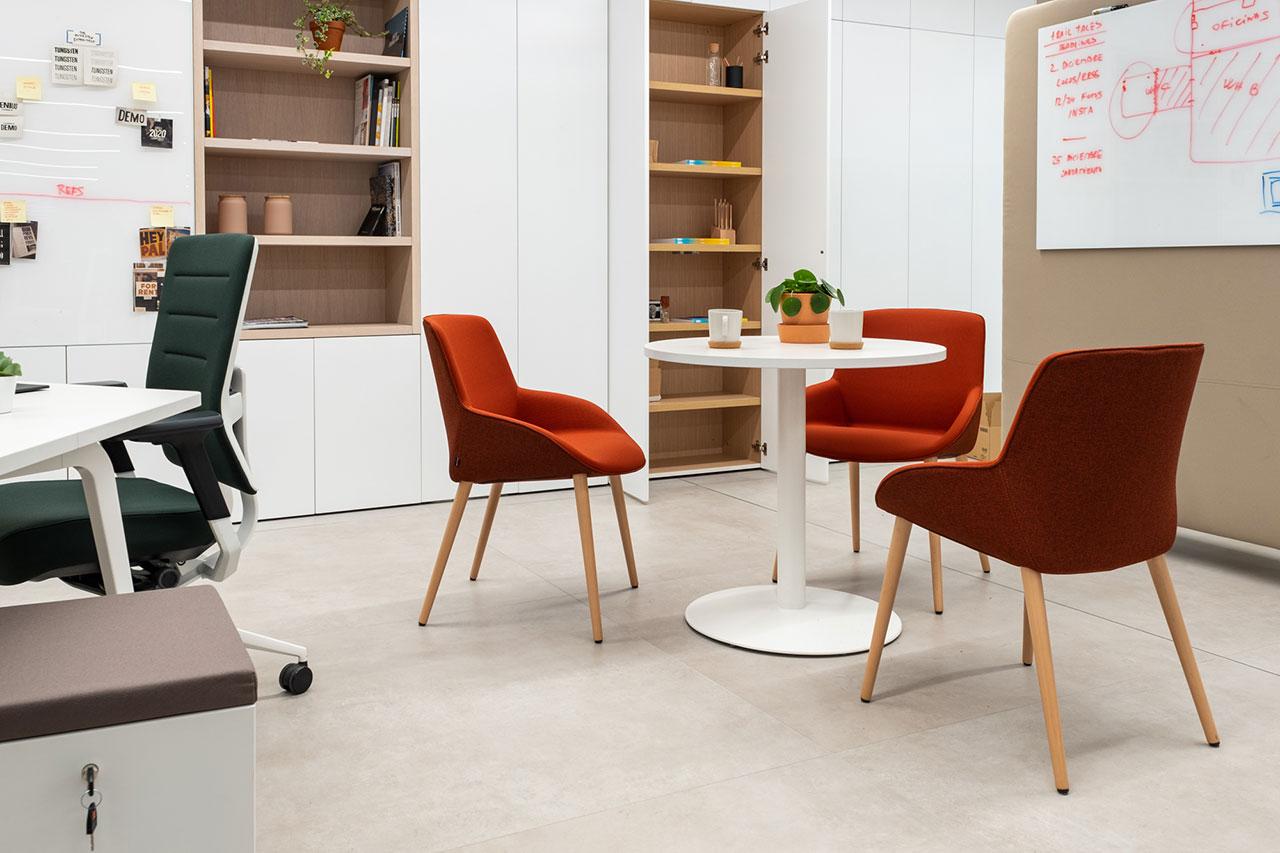 cervene rokovacie stolicky a biely okruhly stol v kancelarii pre kolaboraciu