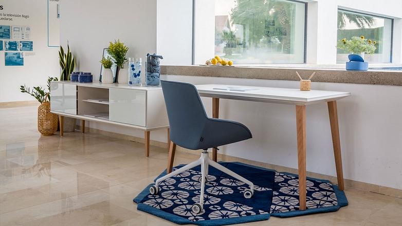 domace pracovisko s modrym kobercom a prirodnym stolom a modrou stolickou na kolieskach actiu